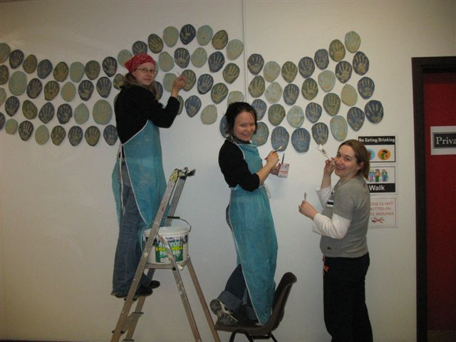 Tiina, Saija and Michelle installing the hand prints. Public Art Project 2006 by ceramic artist Michelle Maher & the children, staff & parents at St. Patrick's N.S., Diswellstown, Dublin 15 - to commemorate the opening of their new school. Working in collaboration we created a wall piece entitled 'When the hand was lifted from the clay', it comprised of the handprints of almost 450 participants and was installed in the foyer of the new school building. www.ceramicforms.com