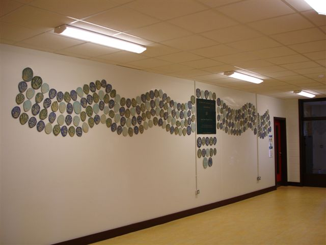 The finished project exhibited over two walls. (Dimensions - 7m x 1.3m) Public Art Project 2006 by ceramic artist Michelle Maher & the children, staff & parents at St. Patrick's N.S., Diswellstown, Dublin 15 - to commemorate the opening of their new school. Working in collaboration we created a wall piece entitled 'When the hand was lifted from the clay', it comprised of the handprints of almost 450 participants and was installed in the foyer of the new school building. www.ceramicforms.com
