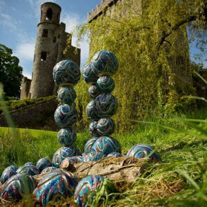 Ceramic outdoor sculpture - Surface Tension by Michelle Maher. This ceramic sculpture was inspired by the science of bubbles and is shown here at Blarney Castle, Co.Cork for Sculpture at the Castle 2014. It was hand built with Sgraffito marks using a grogged crank clay body and high fired in an electric kiln to 1260°C (Cone 8). www.ceramicforms.com Photo by Christian Haubold https://bridgemountphoto.com/, with permission.