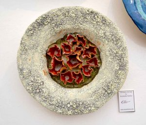 Ceramic wall sculpture by Michelle Maher. This wall piece is inspired by coral and fungi forms; volcanic glaze surface with glass detail. Hand sculpted and modelled in a grogged stoneware clay body and fired in an electric kiln to 1260°C (Cone 8). www.ceramicforms.com.