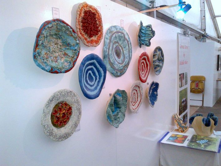 Collection of ceramic wall pieces by Michelle Maher at Art in Action 2014 at Farmleigh House, Dublin. They were hand built and modelled in a grogged stoneware clay body and fired in an electric kiln to 1260°C (Cone 8).See www.ceramicforms.com.